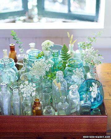 1) Samla ihop tomma glasburkar och -flaskor (senapsburkar, parfymflaskor och så vidare), och packa dem tätt på en fin bricka. Sätt blommor och kvistar i några av dem och vips har du en fin bordsdekoration.