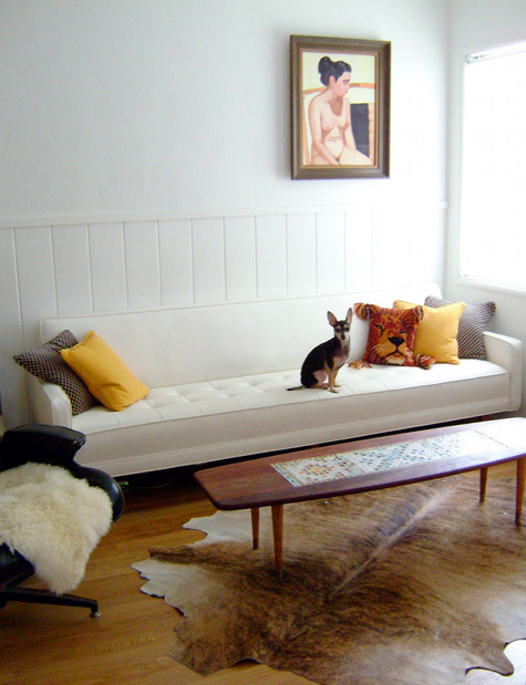 Soffan fick Morgan gratis, och hon klädde om den utan extra kostnad genom att byta lite möbler med försäljaren. Den är klädd i vit vinyl, lätt att torka av. Jag gillar hur hon hängt tavlan också, att bryta symmetri är alltid spännande. (Och SÖT hund!)
