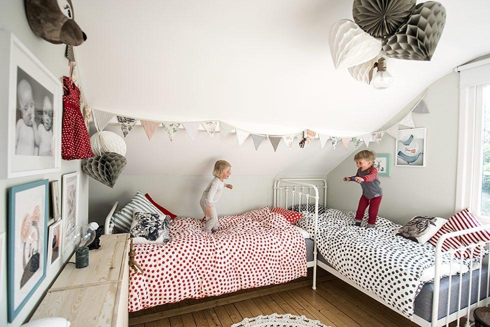 Barnrum med tavelvägg, virkad matta, pompoms, vimplar, järnsängar – Husligheter