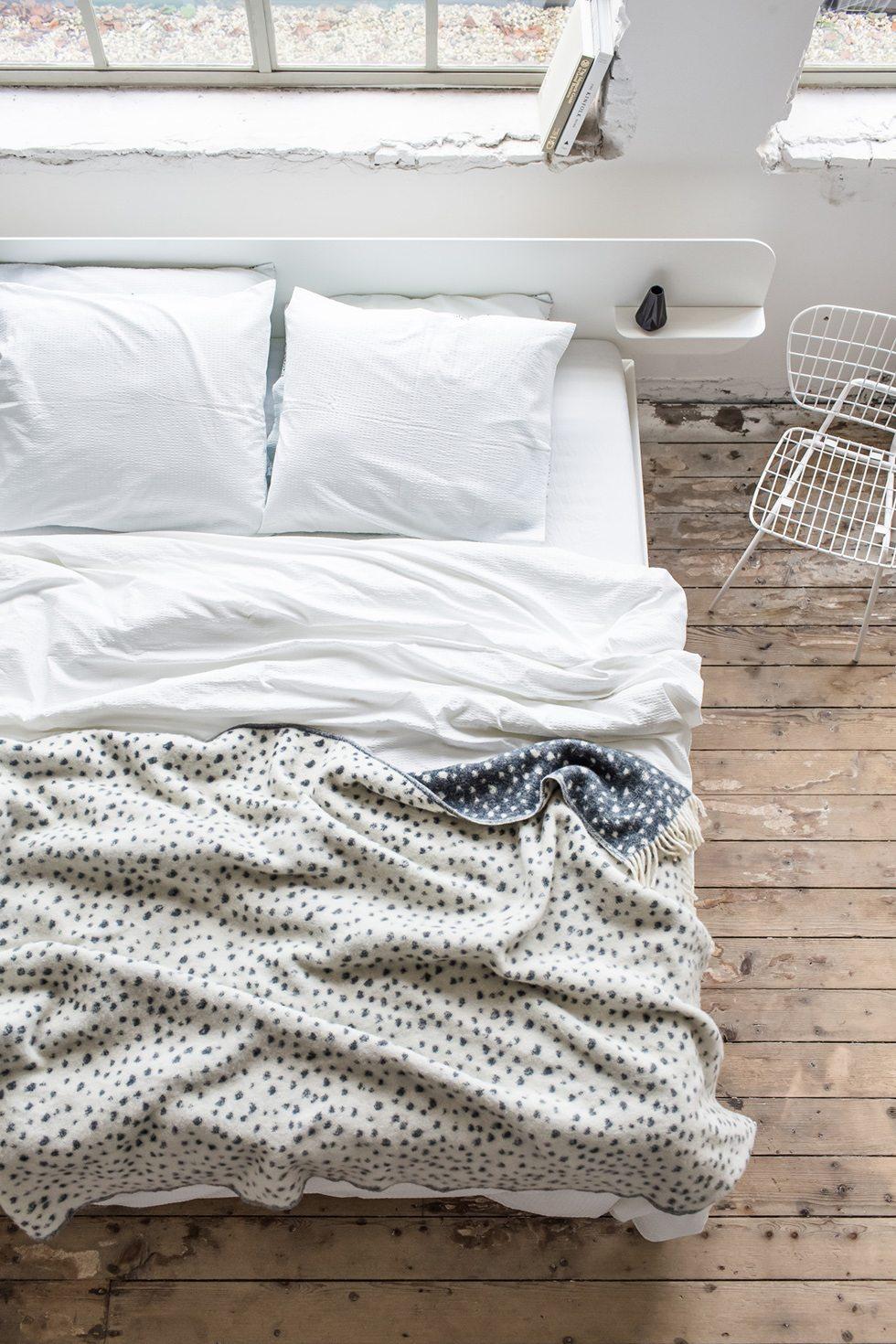 Mönstrat överkast på säng med vita sängkläder – Husligheter