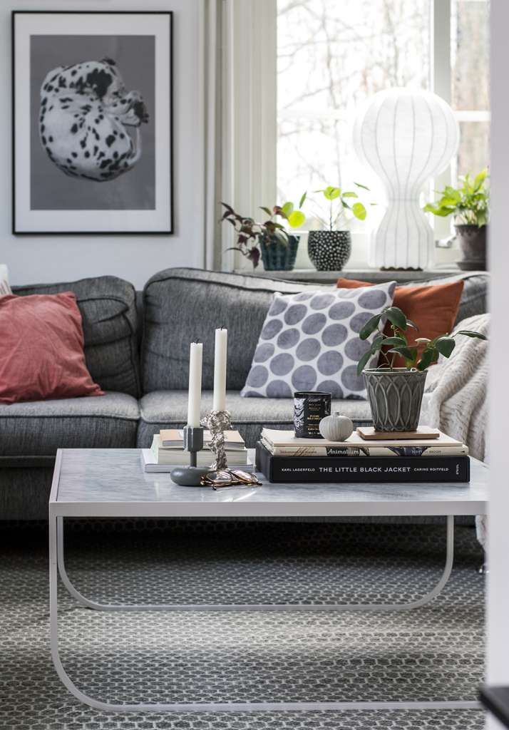 Vardagsrum med ullmatta från Matt-tema, grå soffa, marmorbord och rosa kuddar.