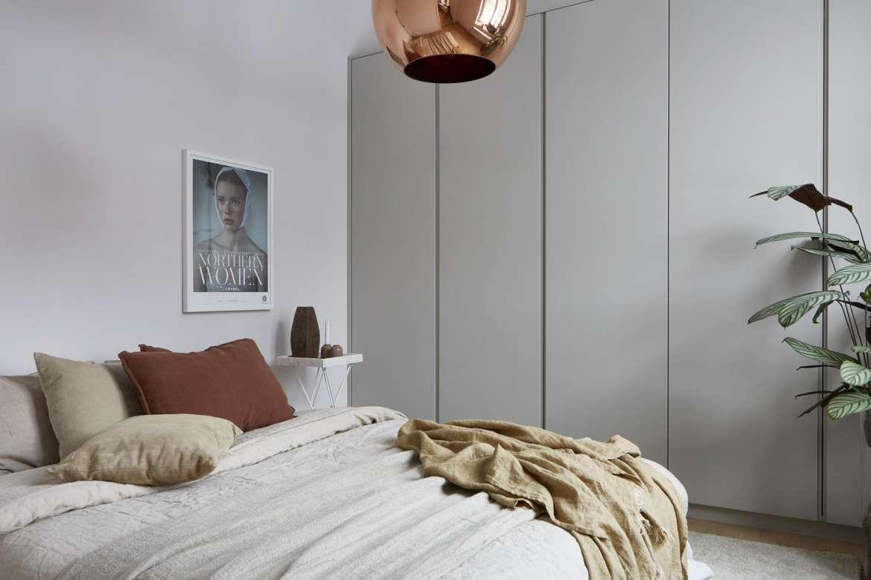 Sovrum med platsbyggda garderober, Tom Dixon-lampa och linnekuddar