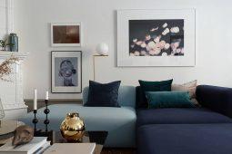 Tavelvägg med konst och blå sammetssoffa